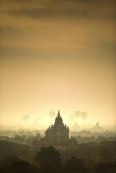 日の出のシーンの熱気球は、バガンミャンマーのパゴダの古代都市の畑を飛ぶ。