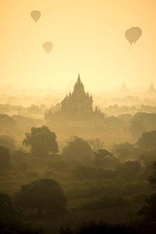 Sunrise scene hot air balloons fly over pagoda ancient city field in bagan myanmar.