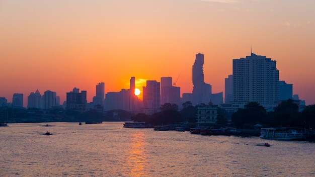 Sunrise over the scenic skyline at bangkok, thailand, viewed in backlight at sunrise with orange red clear sky.