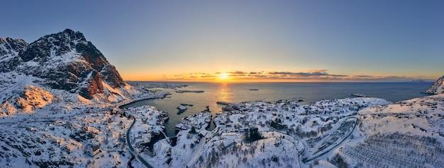 Sunrise over the sea illuminating a small norwegian fishing village. breathtaking aerial view.