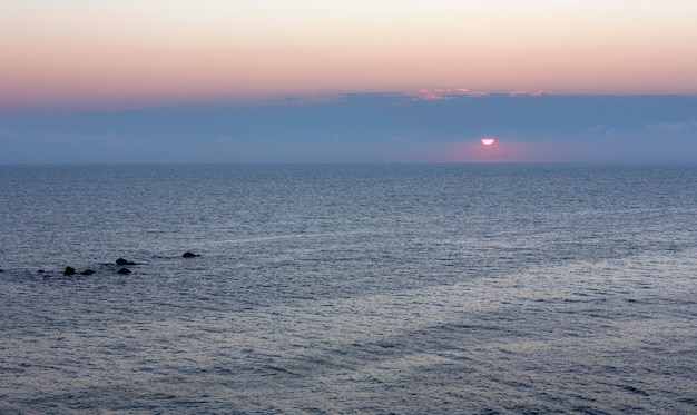 空の太陽と水の上の水中の岩の上にある日の出の海の風景。