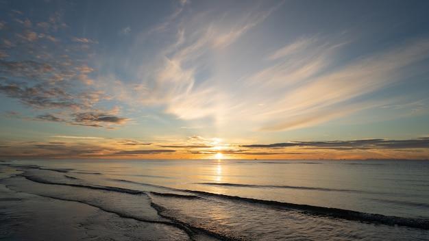 日の出は海と美しい雲の上を撮影しました。太陽は海の上の大きな雲の後ろに消えました。