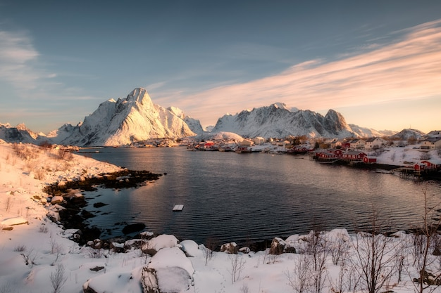 Sunrise on snowy mountain with scandinavian village at coastline in winter
