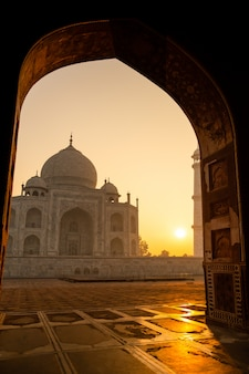 Sunrise of taj mahal through an archway in agra india shot in high iso.