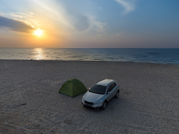 Sunrise over the tent standing on the beach, the sandy beach and tourists resting in a tent next to the car.