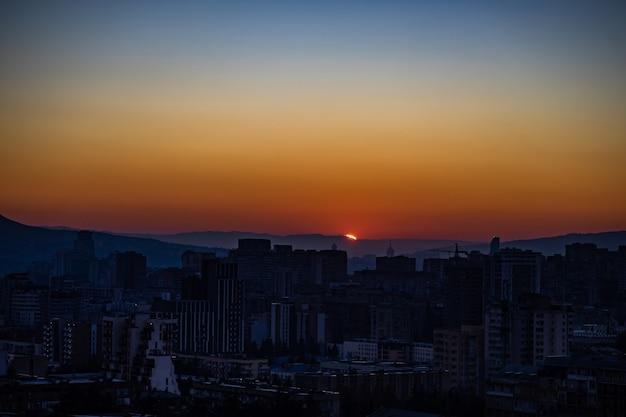 밝은 푸른 하늘과 붉은 태양이있는 트빌리시 시내의 일출 시간