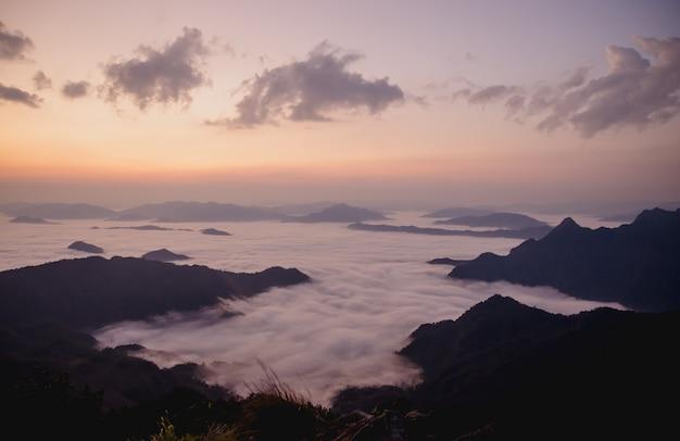 Sunrise with dark mountain and mist