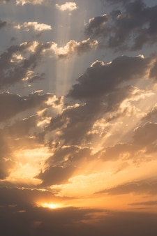 Sunrise with dramatic dark clouds and light rays through clouds at sky