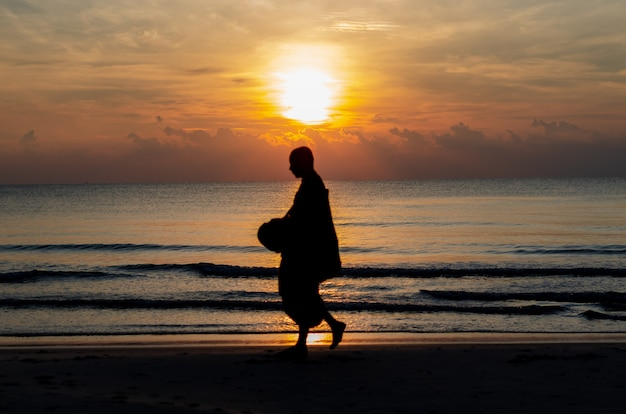 Sunrise with reflection on the sea and beach that have blurred silhouette photo of buddhist monk.