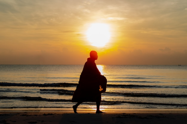 Sunrise with reflection on the sea and beach that have silhouette photo of buddhist monk.