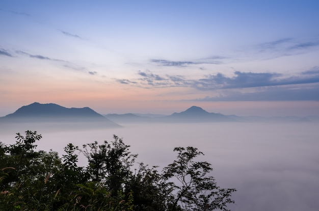 Sunrise with sea of fog over phu thok mountain at chiang khan in loei, thailand