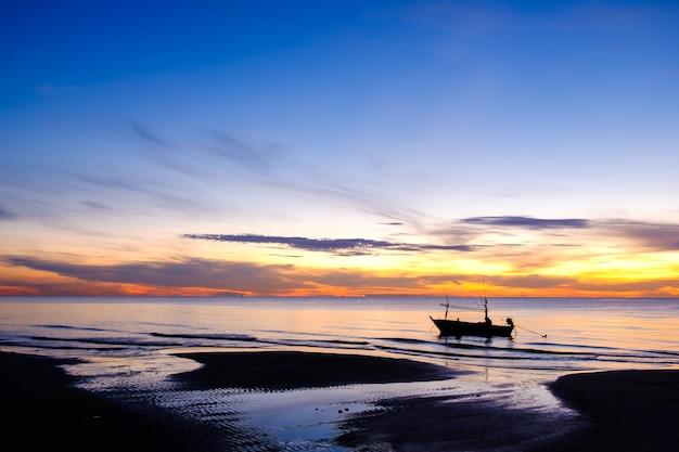 Восход солнца с силуэт рыбацкой лодки на пляже