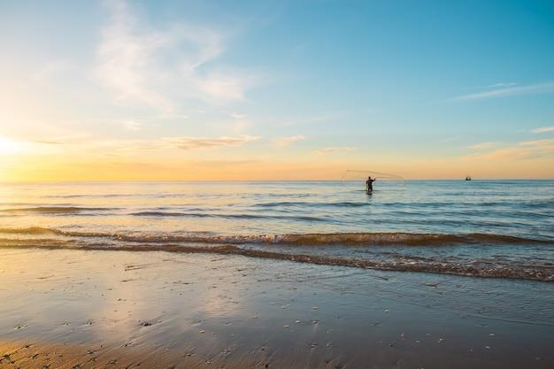 Восход солнца с силуэтом рыбака на пляже