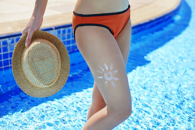 Sunscreen and beautiful female feet in the summer pool, the concept of protecting the skin