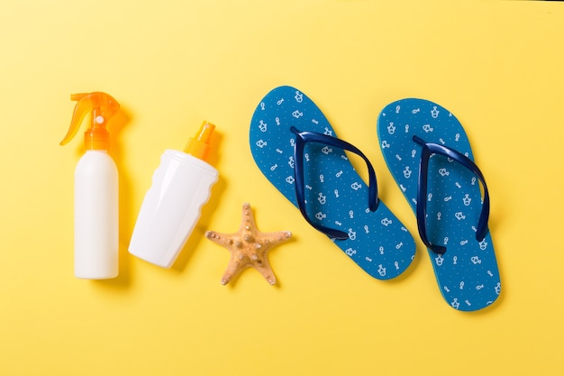 Sunscreen bottle or body spray on yellow background top view