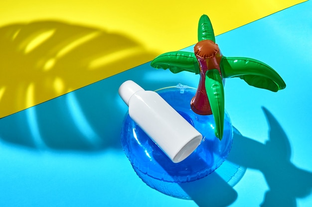 日焼け止めのボトルは、海の膨脹可能な円と砂浜のヤシの葉の影に浮かんでいます。モックアップ。クリエイティブなミニマルコンセプト。