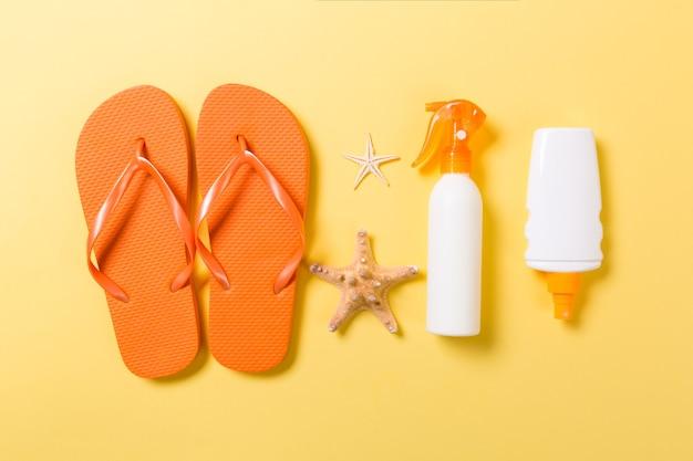 黄色の背景の上面図に日焼け止めボトルまたはボディスプレーを平らに置き、コピースペースを付けます。ビーチの海のアクセサリーと休日の休暇旅行のコンセプト。