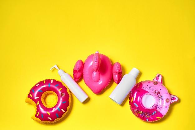 日焼け止めボトルと黄色の背景に膨らませてピンクのドーナツ、フラミンゴ、キティ。クリエイティブなミニマルコンセプト。上面図フラットレイ
