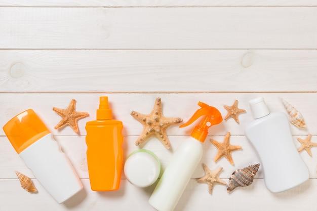 Солнцезащитные бутылки с ракушками на белом деревянном столе. вид сверху аксессуары для здравоохранения путешествия.