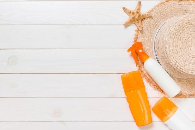 Солнцезащитные бутылки с морскими звездами и шляпой от солнца на белом деревянном столе с копией пространства. вид сверху аксессуары для здравоохранения путешествия.