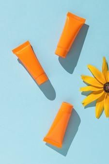 Sunscreen and a bright flower on a blue background. flat lay.