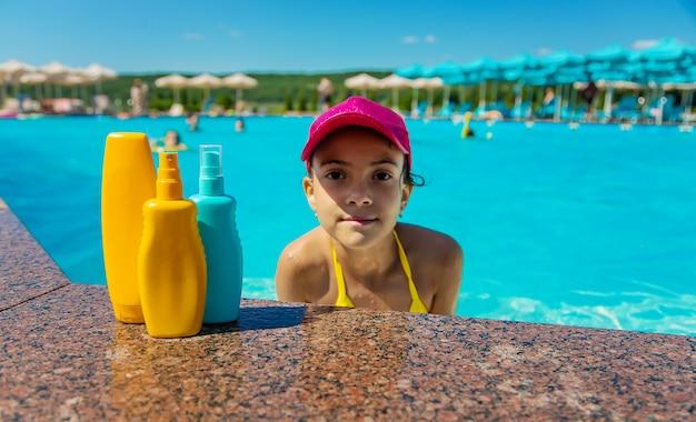 子供用プールのそばの日焼け止め。セレクティブフォーカス。