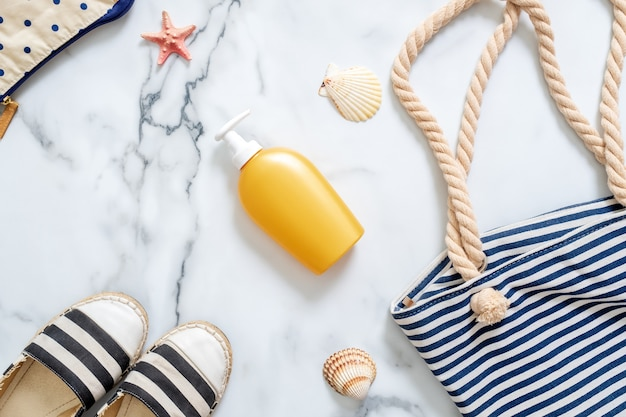 Sunscreen cream bottle, striped beach bag, seashells on marble background.