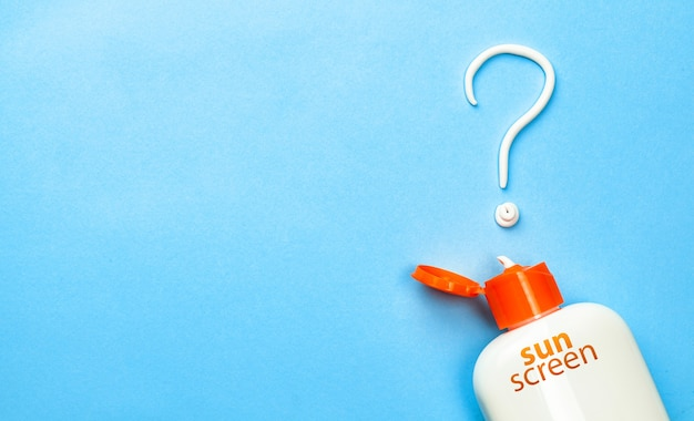 Sunscreen cream in the form of question mark on blue background with white tube