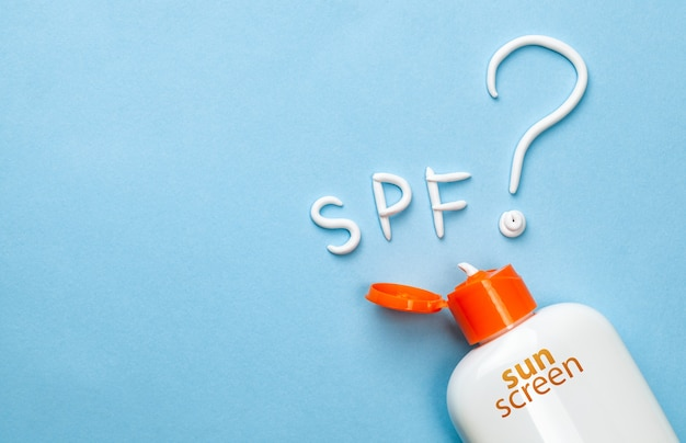 Sunscreen. cream in the form of question mark and the inscription spf on blue background with white tube. concept of how to choose sunblock.