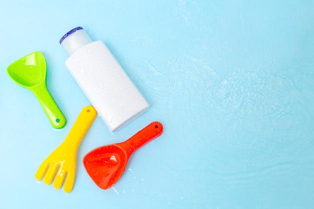 Sunscreen cream to kids skin from sun with colorful water toys on blue water