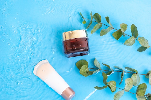 Sunscreen cream spf lotion to skin with eucalyptus leaves on blue water pool