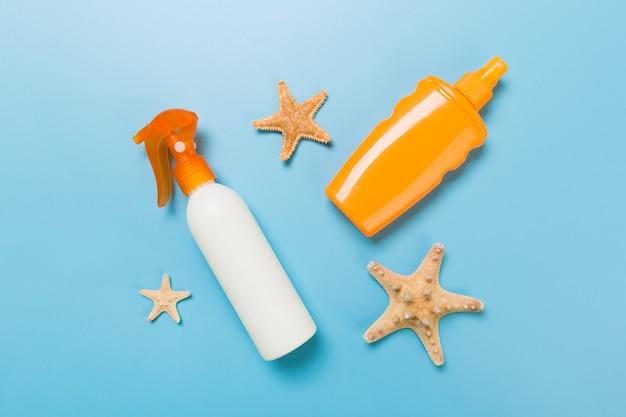 青い背景、上面図のボトルにヒトデと貝殻の日焼け止めクリーム