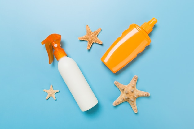 Sunscreen cream with starfish and seashells in bottles on blue background, top view