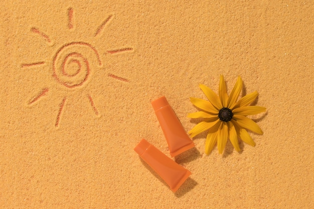 Sunscreen, a flower and a painted sun on the sand.