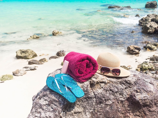 Sunscreen, hat, glass, shoes on stone with sea background. summer and holiday concept.