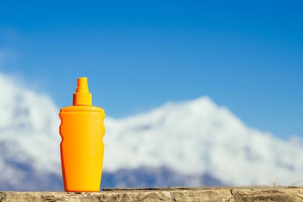 산 배경에 오렌지 병에 썬크림. 피부암을 예방하고 산에서 자외선 차단제를 사용한다는 개념.