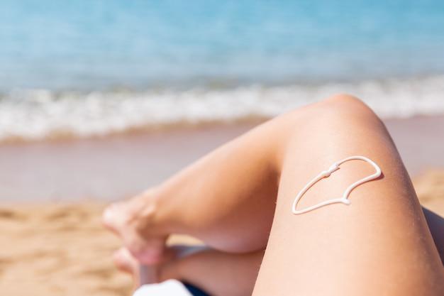 바다로 수건에 일광욕을하는 여성의 다리에 심장 형태의 자외선 차단제.