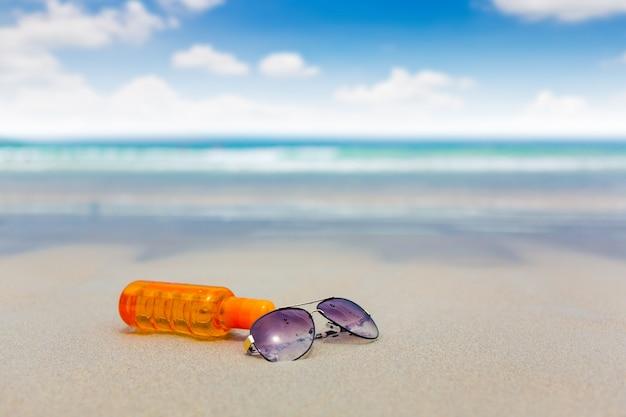 여름철 해변에서 자외선 차단제 로션 및 어두운 안경