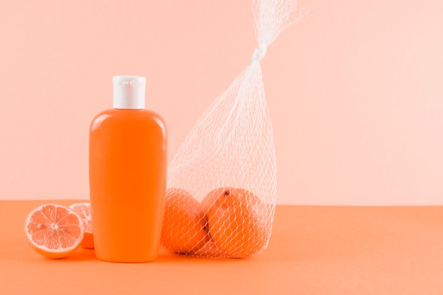 Sunscreen lotion bottle and grapefruits on colored backdrop