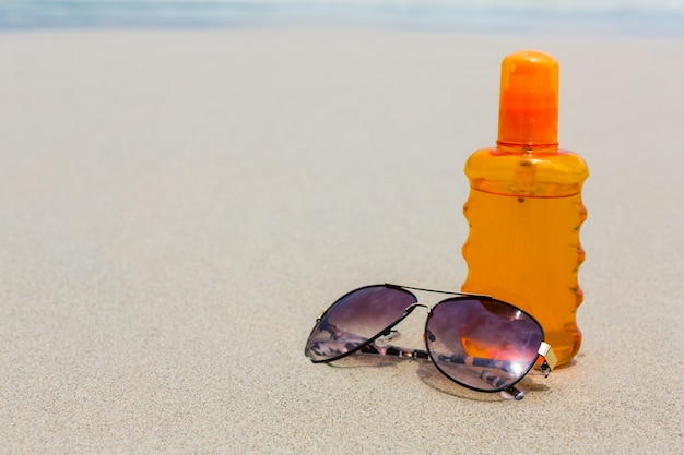Sunscreen lotion and dark glasses on the beach for summer time