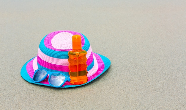 Sunscreen lotion and dark glasses with hat on the beach for summ