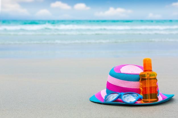 Crema solare e occhiali scuri con cappello sulla spiaggia per summ