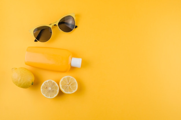 Sunscreen lotion; lemons and sunglasses on yellow background
