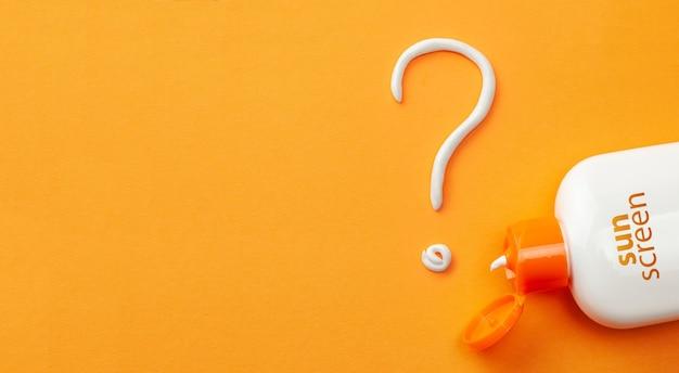 Солнцезащитный крем на оранжевом фоне. пластиковая бутылка солнцезащитного крема и белого крема в виде вопросительного знака. как выбрать солнцезащитный крем.