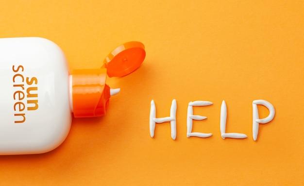 オレンジ色の背景に日焼け止め。ヘルプという言葉の形で日焼け止めと白いクリームのプラスチックボトル。