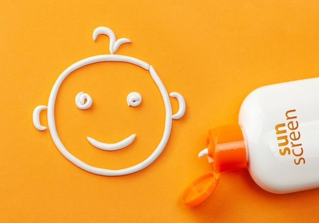 オレンジ色の背景に日焼け止め。日焼け止めのペットボトルと笑顔の赤ちゃんの顔の形をした白いクリーム。子供のためのクリーム。