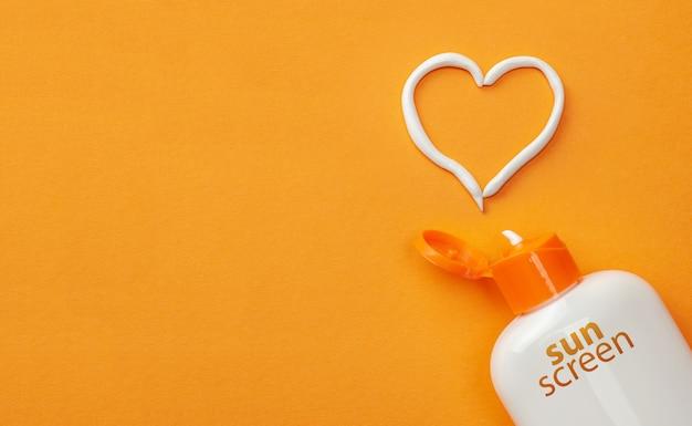 오렌지 배경에 자외선 차단제입니다. 태양 보호 플라스틱 병과 흰색 하트 모양의 크림.