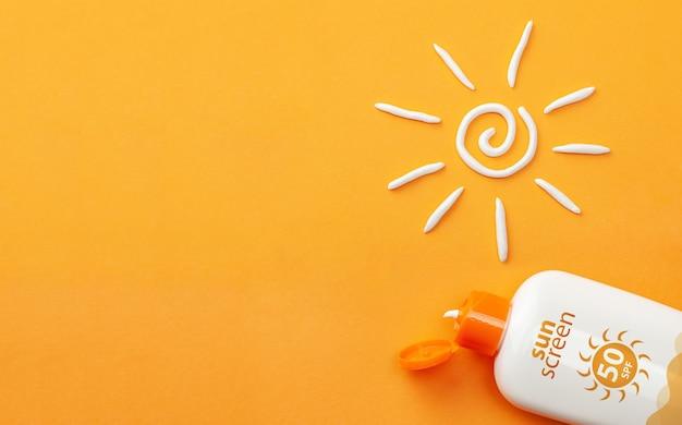 오렌지 배경에 자외선 차단제입니다. 태양 보호 플라스틱 병과 흰색 태양 모양 크림.
