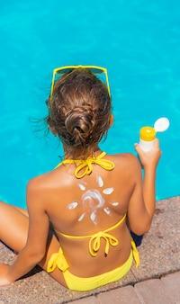 子供の背中の日焼け止め。セレクティブフォーカス。