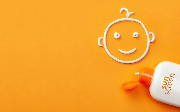 Sunscreen on orange background plastic bottle of sun protection and smiling baby face